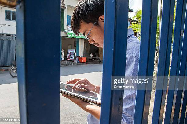 A young Cambodian man uses a tablet to check social media on April 9 2014 in Phnom Penh Cambodia Leaked to the media today the draft of Cambodia's...