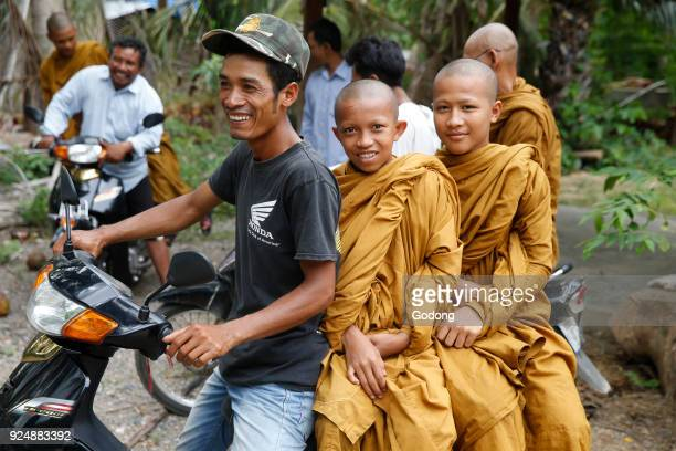 Young Cambodian monks traveling on scooters in Battambang province Cambodia
