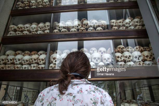 A young Cambodian woman looks at the main stupa in Choeung Ek Killing Fields which is filled with thousands of skulls of those killed during the Pol...