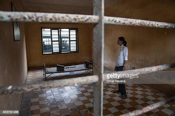 Young Cambodian woman stands in one of the torture rooms of Tuol Sleng prison, also known as S-21, after the announcement of the verdict for former...