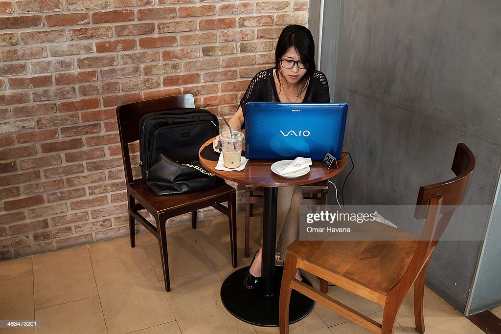 A young Cambodian woman uses her laptop in a local restaurant on April 9, 2014 in Phnom Penh, Cambodia. Leaked to the media for the first time on 9 April 2014, the draft of Cambodia's first-ever cybercrime law, in the pipelines since May 2012, is being criticised by international and local human rights organisations for severely restricting freedom of expression online. Article 28 in particular is being criticised for including vague provisions that could be used to silence Cambodian citizens, such as Article 28(3), which prohibits publications 'deemed to generate insecurity, instability and political cohesiveness,' and Article 28(4), which prohibits publications which 'slanders or undermined the integrity of any governmental agencies.' Both of these provisions carry with them sentences of 1 to 3 years in prison. Internet penetration has drastically increased in recent years and is increasingly serving as an outlet and as a source of information in a country where most media are controlled by the ruling party. Cambodia's government is already under criticism for recent crackdowns on protests and human rights activists, and is accused of frequently using provisions in the Criminal Code and other legislation to unjustly silence civil society and journalists. Human rights activists fear that this new law will exacerbate the situation and provide the government with additional tools to silence its critics online.