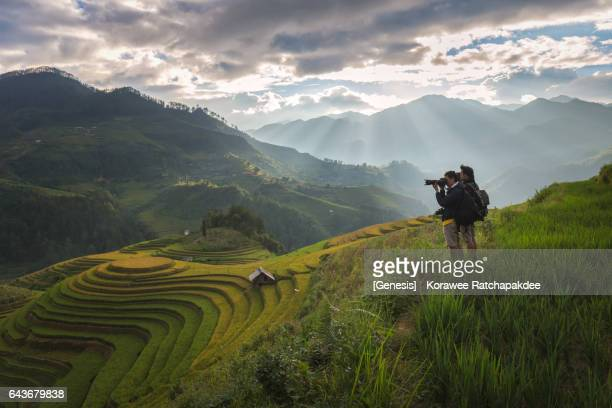 a young camera man taking a photo at the rice field in the sunlight - reisterrasse stock-fotos und bilder