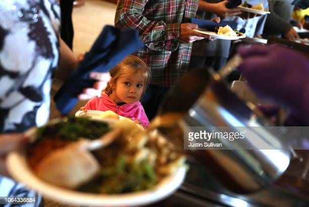 A young Camp Fire evacuee waits in line to receive a free Thanksgiving meal at Sierra Nevada Brewery on November 22 2018 in Chico California Fueled...