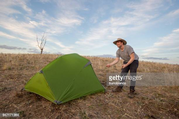 Young camping man adjusts a rope off his tent