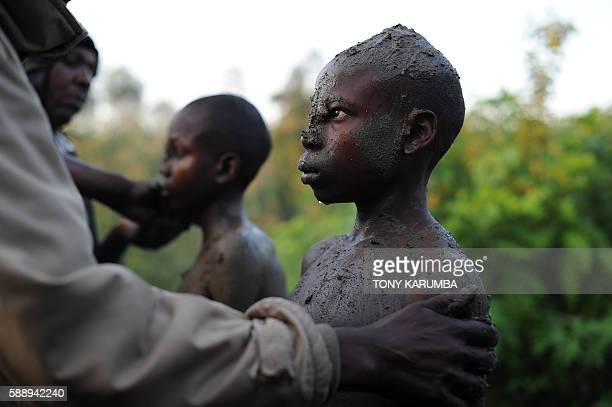 Young candidates for a traditional circumcission rite are smeared with mud on August 11, 2016 at the start of a ceremony that culminates in the...