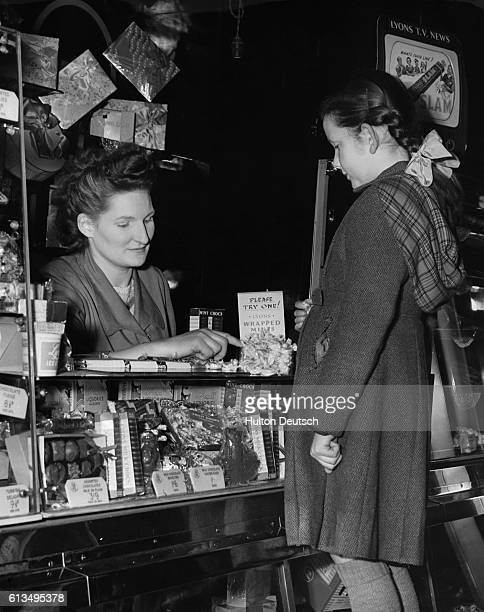 Young candy customer Susan Rennison watches in disbelief as candy store clerk E Groves points to free samples The candy store at Paddington Station...