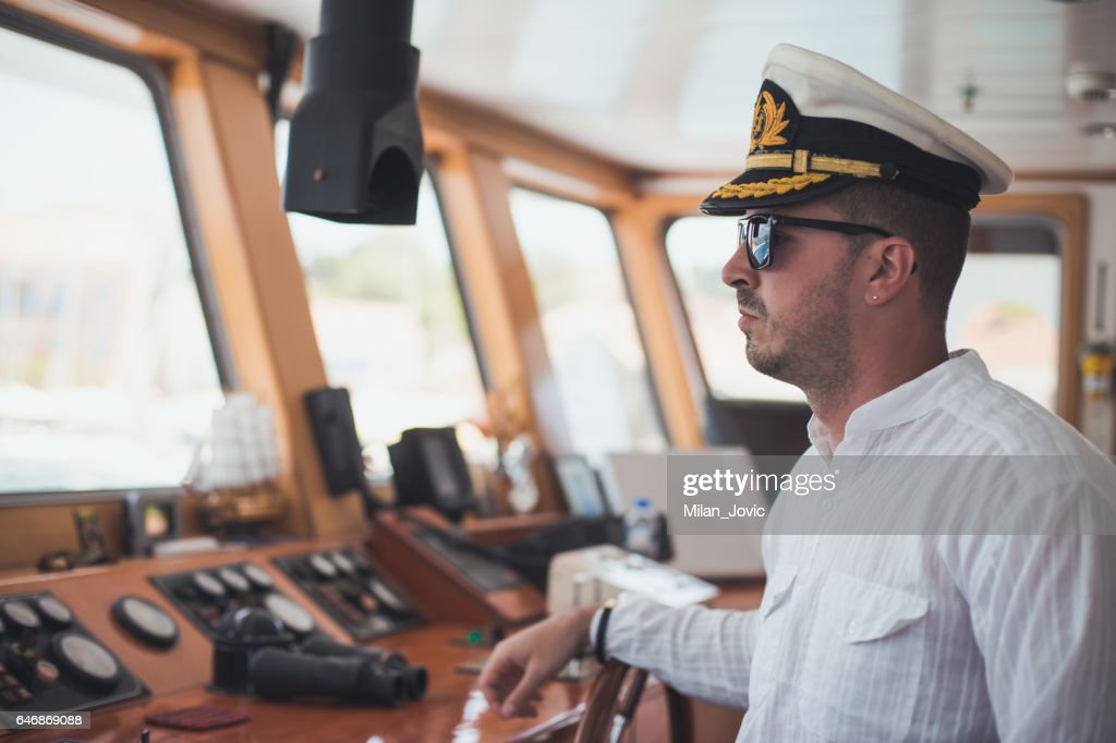 Young captain steering boat : Stock Photo