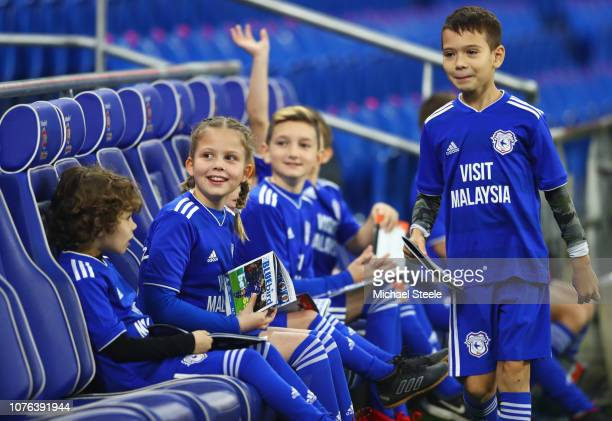 Young Cardiff City mascots sit on the bench prior to the Premier League match between Cardiff City and Tottenham Hotspur at Cardiff City Stadium on...
