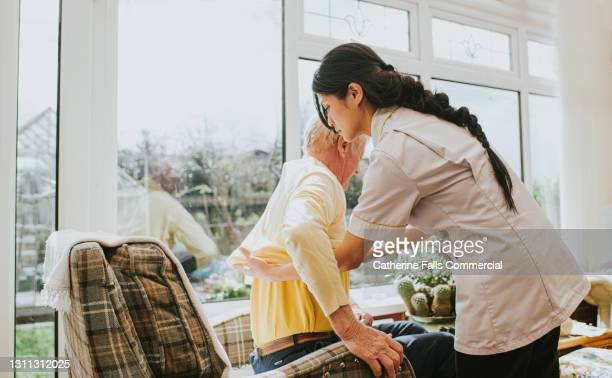 young care assistant helps an elderly gent put on his jumper - support stock pictures, royalty-free photos & images