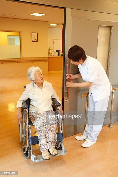 a young care worker holding the door for a senior woman in wheelchair - bend over woman stock pictures, royalty-free photos & images