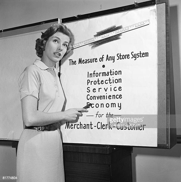 Young career woman giving business presentation, pointing at poster.