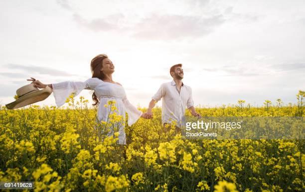 Junge unbeschwerte Paare, die Spaß beim laufen durch die Wiese im Frühling.
