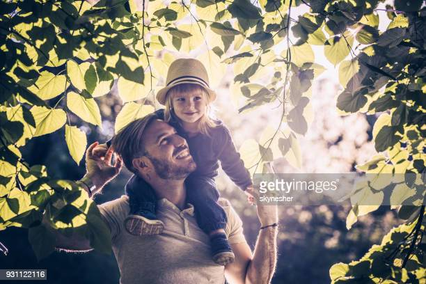 Young carefree father and son enjoying among tree branches in springtime.