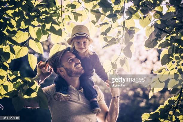 Joven despreocupado padre e hijo disfrutando entre ramas del árbol en primavera.