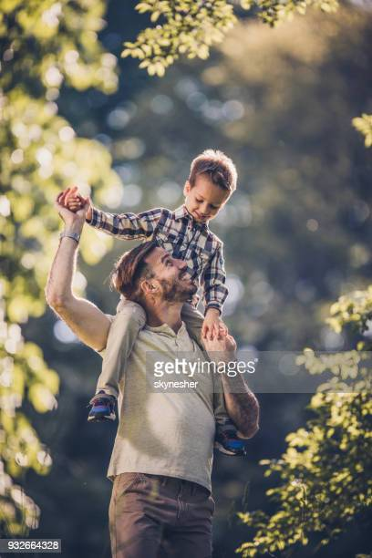 young carefree father having fun while carrying his small son on shoulders in nature. - carrying on shoulders stock pictures, royalty-free photos & images