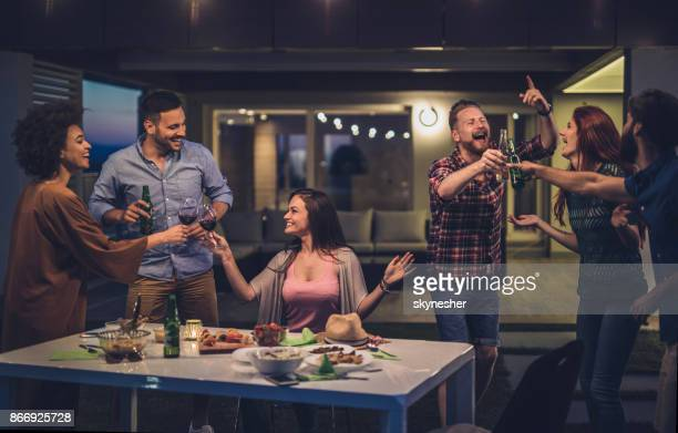 young carefree people having fun while toasting on a night party in front of their house. - dinner party stock pictures, royalty-free photos & images