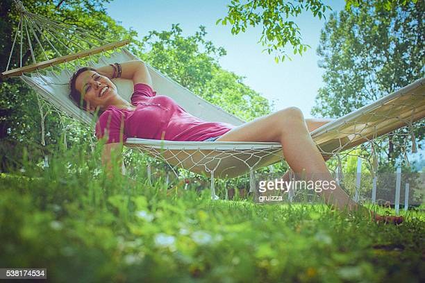 young carefree woman relaxing in a hammock in the garden - hammock stock pictures, royalty-free photos & images