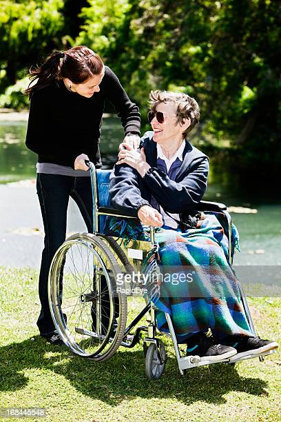 Young caregiver and old woman in wheelchair holds hands affectionately