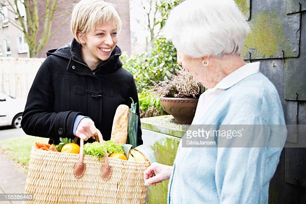 young caregiver bringing purchases to senior woman
