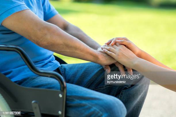 young caregiver holding seniors hand - obscured face stock pictures, royalty-free photos & images