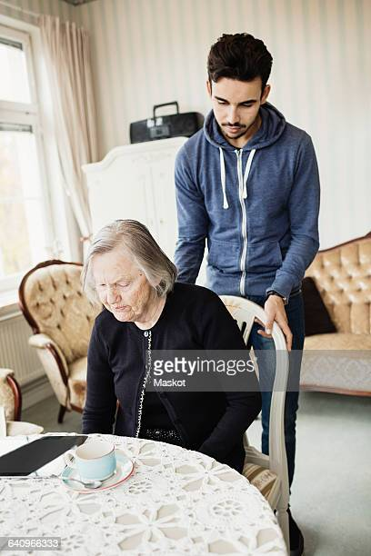 Young caretaker adjusting chair for senior woman in living room at nursing home