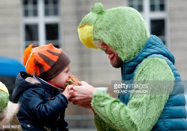 A young carnival enthousiast shares a burger with his father during street carnival in Duesseldorf western Germany on Carnival Sunday February 26...