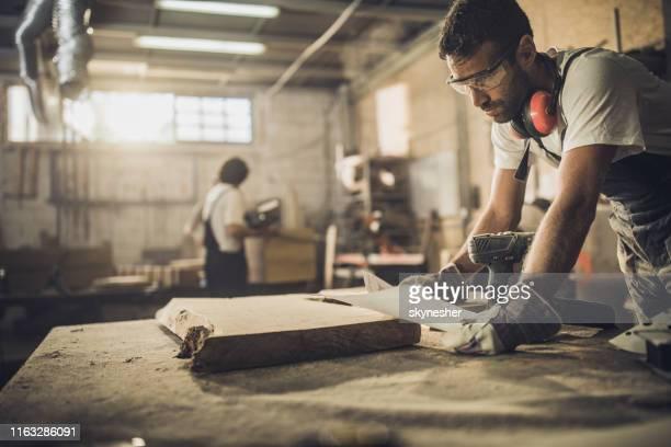 junger zimmermann analysiert designpläne, während er möbel in einer werkstatt herstellt. - designer einrichtung stock-fotos und bilder