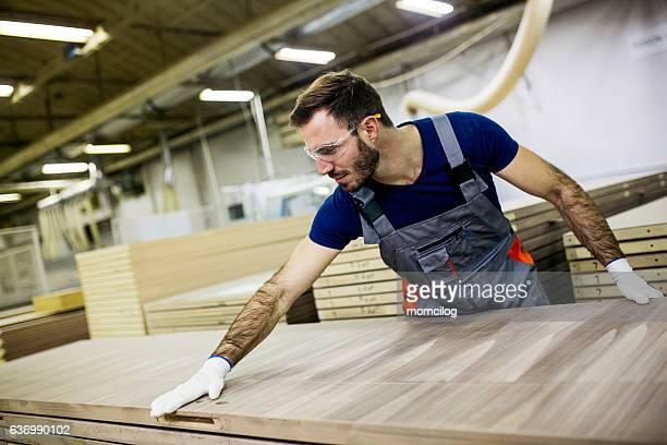 young carpenter carrying wood plank - mobília imagens e fotografias de stock