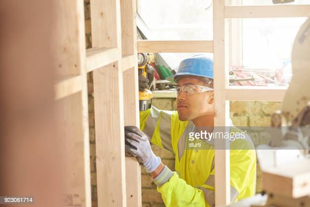 young carpenter fixing studwork - black glove stock pictures, royalty-free photos & images