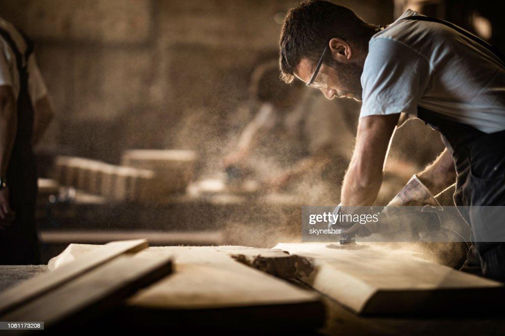 若い大工のサンダーを使用して木の部分に取り組んでいる間。 : ストックフォト