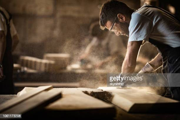 young carpenter using sander while working on a piece of wood. - legno foto e immagini stock