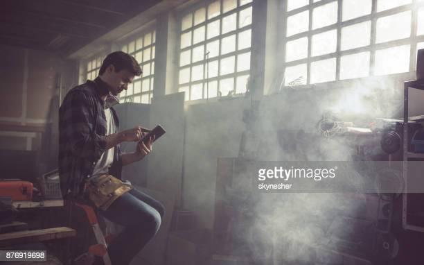 Junge Tischler mit Touchpad in Tischlerei.