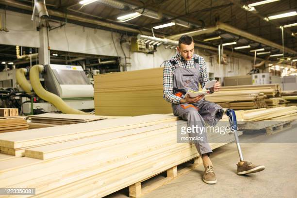 young carpenter with prosthetic leg at the factory lifting wood plank - persons with disabilities stock pictures, royalty-free photos & images