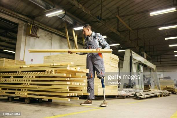 ウッドプランクを運ぶ仕事で義足を持つ若い大工 - 四肢切断 ストックフォトと画像