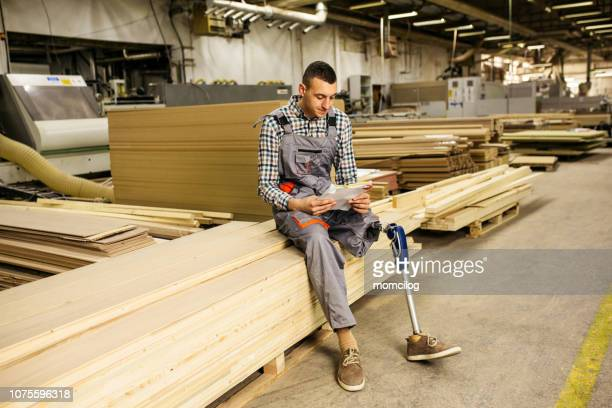 young carpenter with prosthetic leg at work - artificial limb stock pictures, royalty-free photos & images