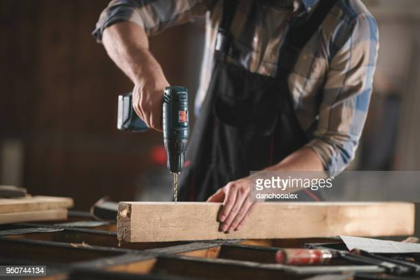 young carpenter working in his workshop - drill stock pictures, royalty-free photos & images