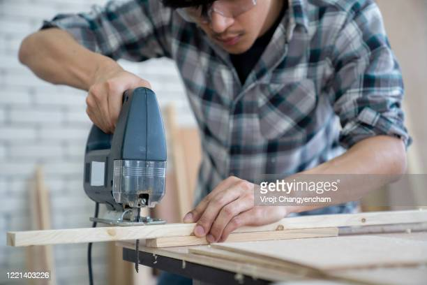 young carpenter working sawing wood by electric jigsaw. - 電動糸のこ ストックフォトと画像