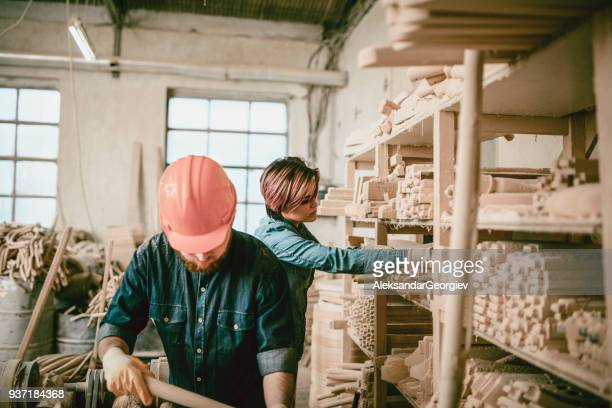 Young Carpenters Arrange the Wooden Chair Sample Parts on Shelf in Wood Factory
