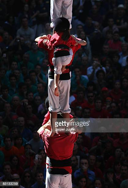 A young casteller of the Colla Jove Xiquets de Tarragona 'colle' climbs up building a human tower during the 22nd Tarragona Castells Competition on...