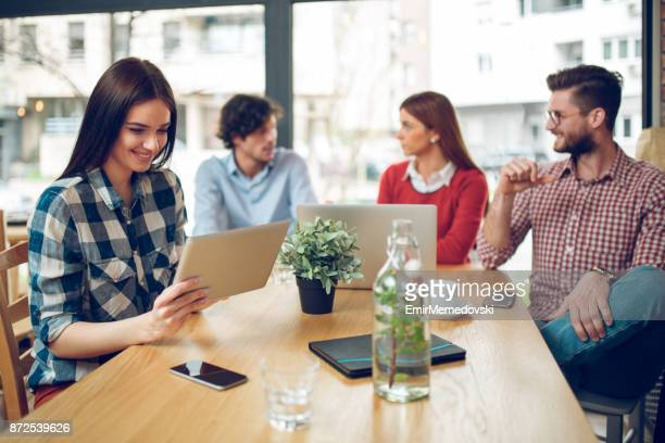 young casual business woman using digital tablet in cafe. - emir memedovski stock pictures, royalty-free photos & images