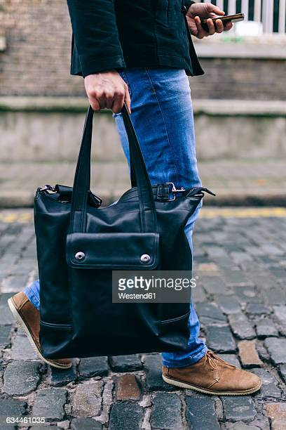 Young casual businessman carrying bag and using mobile phone, low section