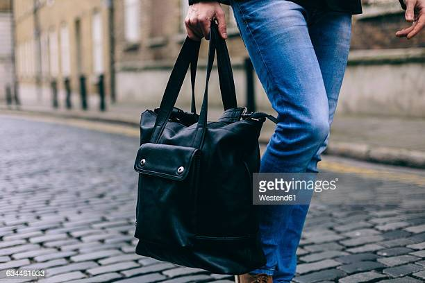 young casual businessman carrying bag, low section - shoulder bag stock pictures, royalty-free photos & images