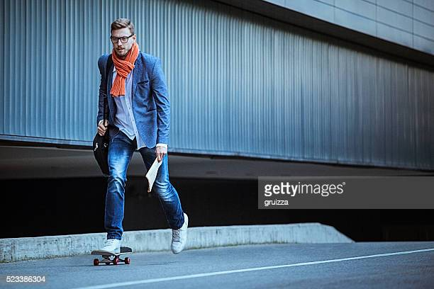 Young casual businessman comuting to work skateboarding.