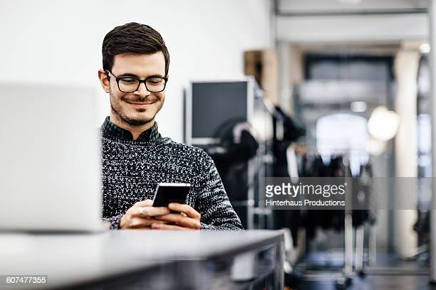 Young casual businessman looking at his smartphone