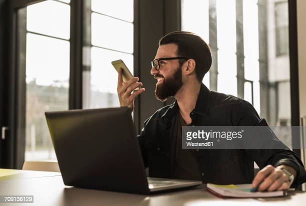 Young casual businessman sitting in office, leaving a voice mail with his smart phone