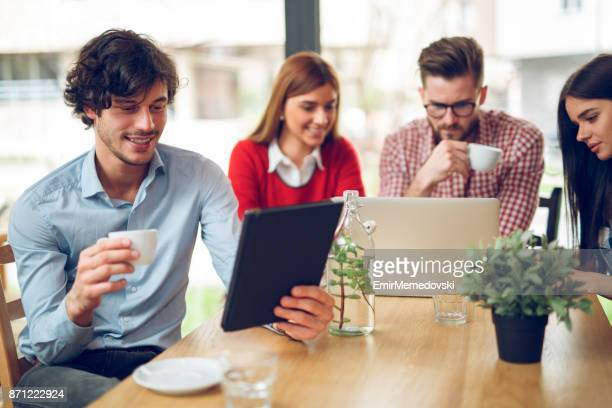 young casual businessman using digital tablet during coffee break. - emir memedovski stock pictures, royalty-free photos & images