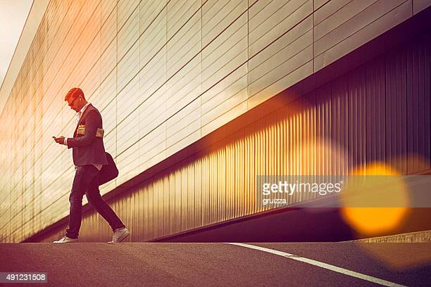 young casual businessman using smartphone in the urban environment - city life stock pictures, royalty-free photos & images