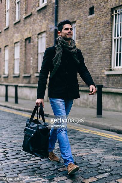 Young casual businessman walking in the street, carrying bag