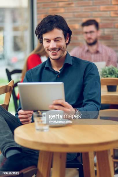 jovem empresário casual com tablet digital, tendo uma pausa para café - figurantes incidentais - fotografias e filmes do acervo