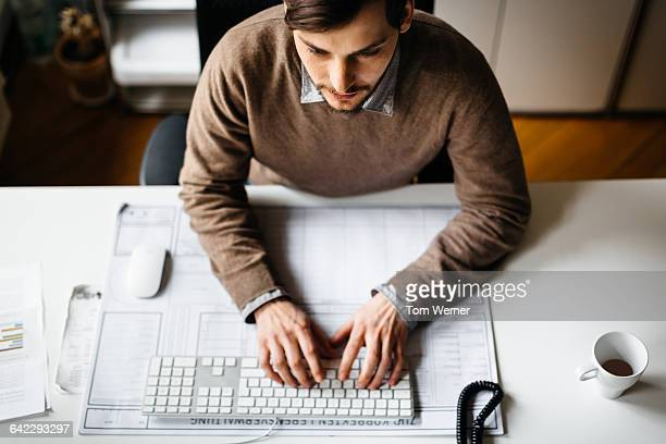 Young casual businessman working on computer